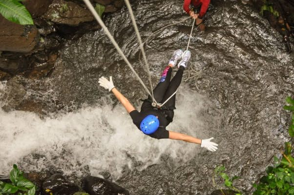 Customer rappelling down the waterfall.